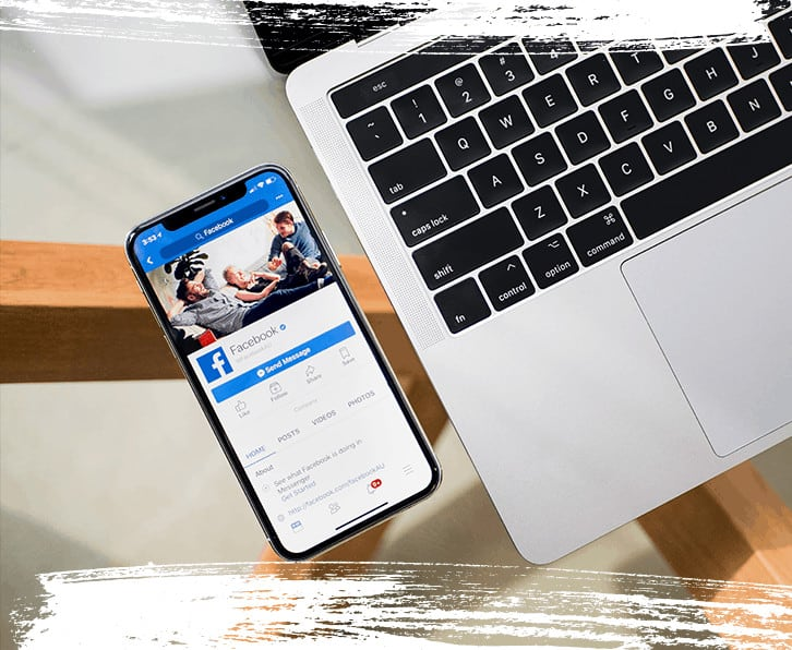 Facebook browsing on a phone with laptop on the right side.